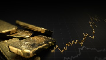 3D illustration of gold ingots over black background with a chart. Financial concept, horizontal image.