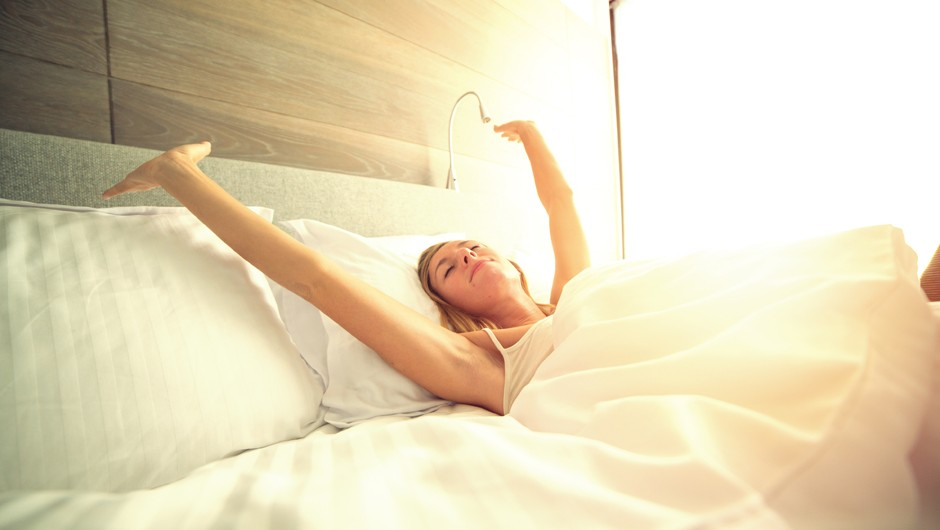 Cheerful young woman waking up in her hotel room, stretching her arms.