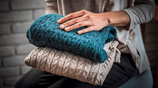Woman's hands holding knitted clothes. Close up. Concept of cozy home.